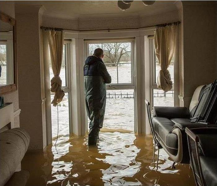 SERVPRO Estimator inspecting damage in flooded home.
